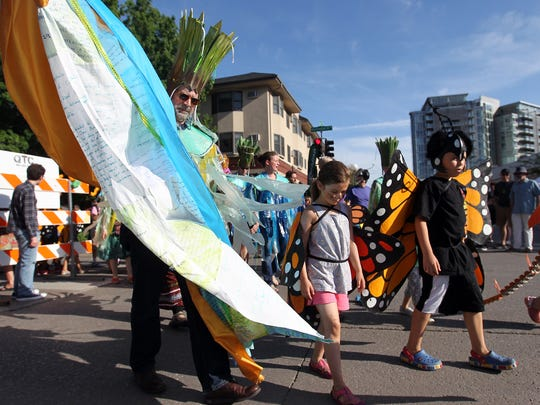 Parade participants march down Washington Street at the Iowa Arts Festival on Friday, June 3, 2016.