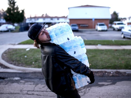 Flint resident Christopher Kabel carries multiple cases of bottled water to help hand out to residents at River Park Apartments in Flint on Monday, April 4, 2016.