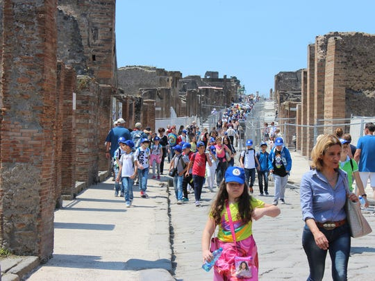 School children and other tourists walk the main streets