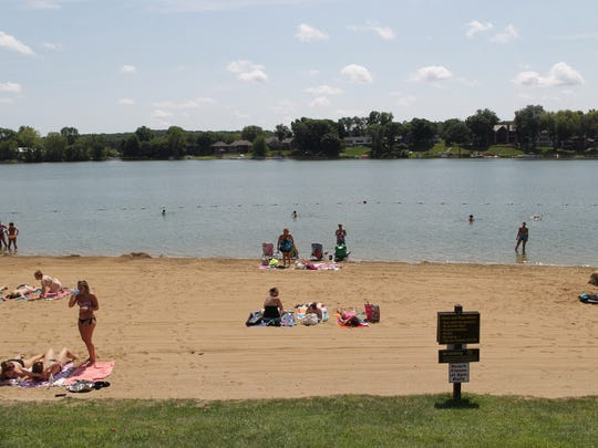 Beach-goers enjoy the sun at Lake Macbride on Thursday,