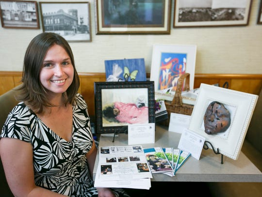 Anna Cottom displays art that will be up for auction