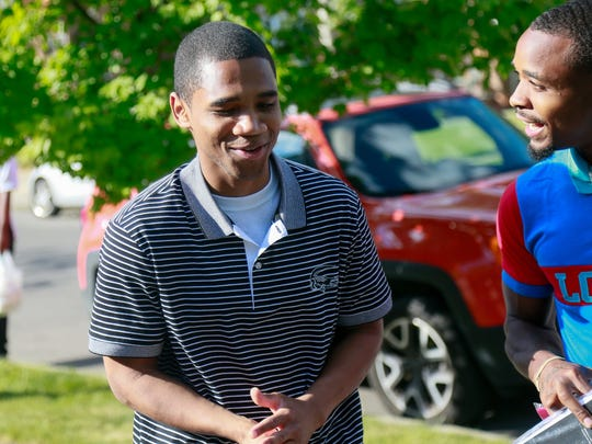 Davontae Sanford, 23, walks up with his brother DeShon Sanford, to greet his family on the lawn his mother's home in Detroit  after being released from prison on Wednesday, June 8, 2016. Devontae was released from prison after serving close to nine years for a quadruple murder officials now believe he did not commit.