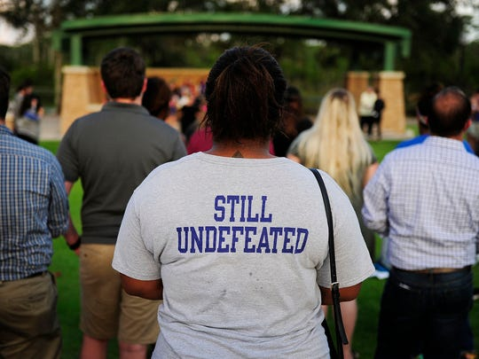Student Callie Rosemeyer of Orlando wears an FGCU Football T-shirt that takes on a new meaning on the evening (FGCU doesn't have a football team) during a vigil Tuesday, June 14, 2016 at FGCU's Veterans Pavilion.