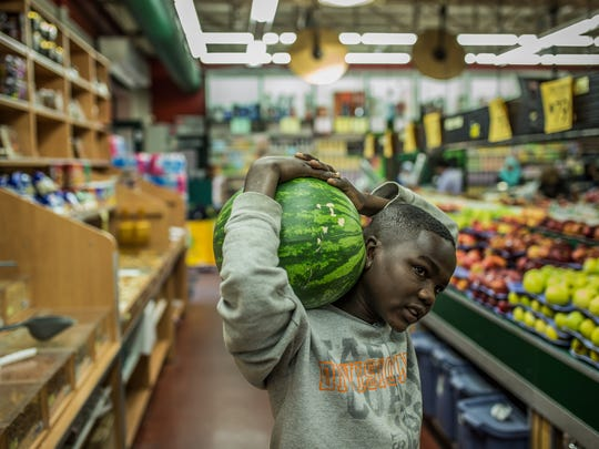 Tahir Yacoub, 15, of Detroit carries a watermelon on his shoulder as he shops with his brother for fruits at Super Greenland Market on Wednesday, May 18, 2016, in Dearborn.