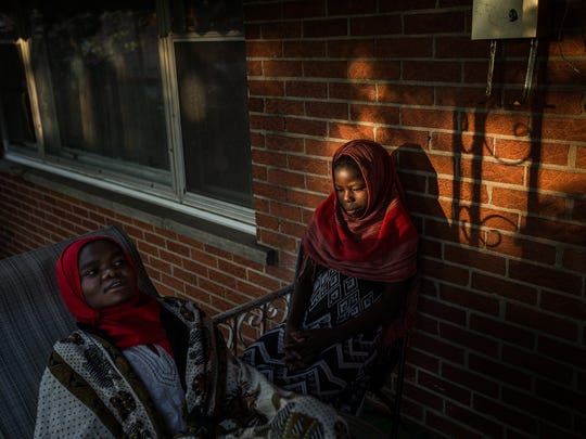 Safia Yacoub, 19, and Guisma Yacoub, 12, sit on the porch of their home on Sunday, May 22, 2016, in Detroit.