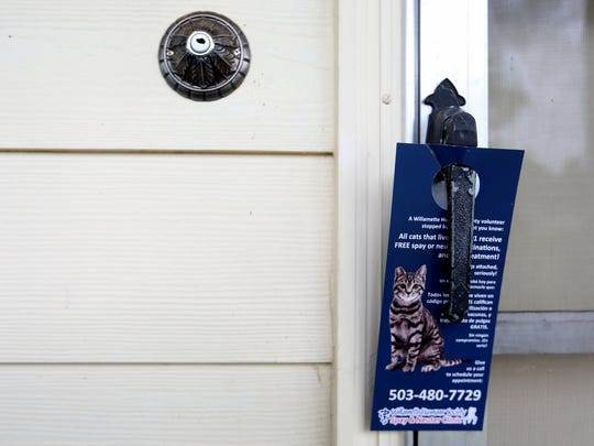 A sign left on a door lets people know about a free spay and neuter program for cats in the 97301 zip code in Salem.