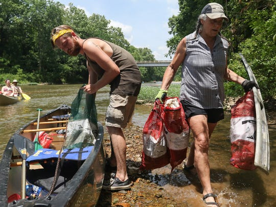 Ben Collins of Willard and Josette Coffman of Highlandville remove  trash and tires from a canoe after a five and a half mile trip down the James River after collecting the trash for the James River Basin Partnership's 18th Annual River Rescue Clean-Up on Saturday, June 18, 2016.