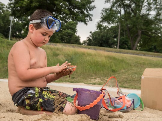Xavier Hart, 7, from Vicksberg plays in the sand at Willard Beach on Monday.