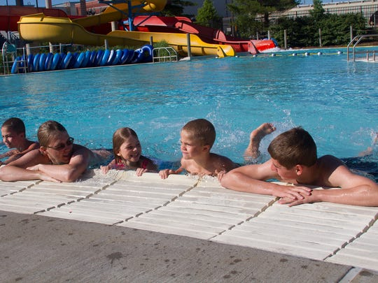 Jacob Mileski, age 9, prepares to learn how to swim with his 7-year-old sister Kristina and 5-year-old brother Jordan. Swimming instructors Ben Smith and Trevor Fuller lead the class at Full Blast.