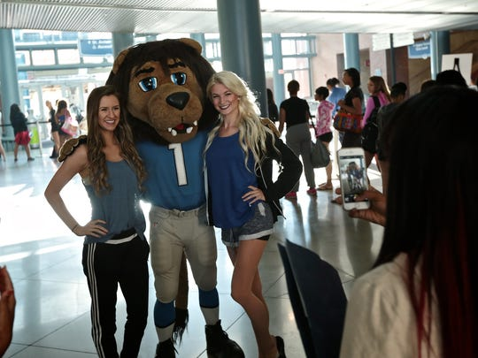 Katie Robbins, left, 21, and Chelsey Korte, 23, both of Novi, pose for a photo with Detroit Lions' mascot, Roary, during the Detroit Lions' cheerleader tryouts on June 25, 2016, at Ford Field in Detroit.