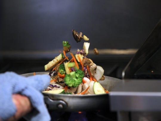 Andy Diep prepares a stir fry dish at Northside Bistro