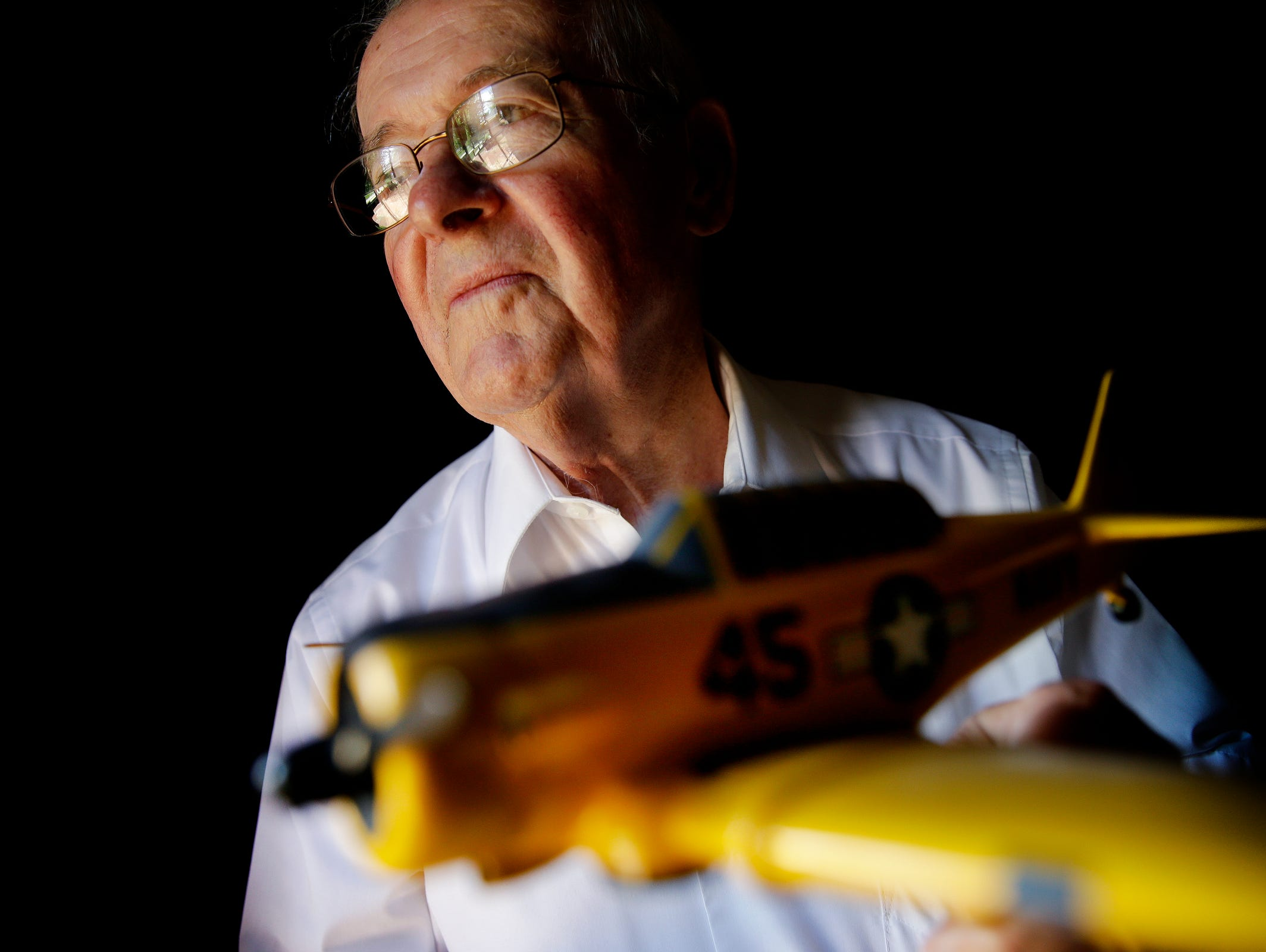 Jim Graham holds a 1/32 scale model of an SNJ-5, the plane in which he trained to become a Navy pilot, inside his Brownsburg home on June 28, 2016.