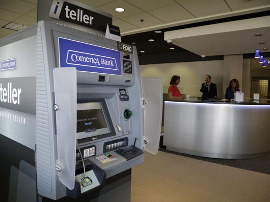 The iTeller at the Comerica Bank in Auburn Hills tested a new customer service pod near the entrance that replaces the traditional teller window, and the iTeller machine allows for face-to-face banking and extended transaction hours until 8pm. It was photographed on Wednesday, August 6,  2014.  l to r: Carol Bonsecour, teller, Joseph Couch, Banking Center Manager Vice President and Susan Czerwinski, teller chat between customers.  Kathleen Galligan/Detroit Free Press
