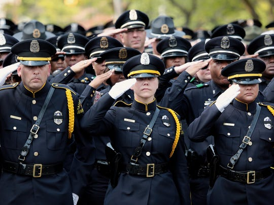 Dallas police officers salute Dallas Police Officer Michael Krol as the casket is carried to the hearse after the funeral mass at St. Robert Bellarmine Catholic Church on Tuesday, July 19, 2016, in Redford Township, MI.