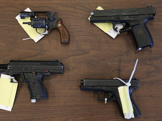Clockwise from top left: A Smith & Wesson revolver, a Smith & Wesson .40-caliber, a Glock .40-caliber and a Hi-Point 9 mm, photographed at the Indianapolis Metropolitan Police Department.