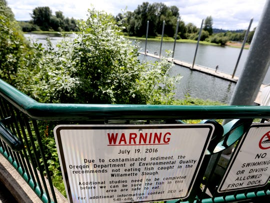 A sign installed by the city warning people of high levels of dioxins in sediment in the Willamette Slough at Riverfront Park in Salem on Tuesday, July 19, 2016.