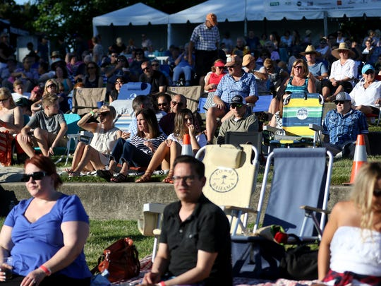 People listen as True North performs in the River Rock Concert Series at Riverfront Park on Wednesday, July 20, 2016.
