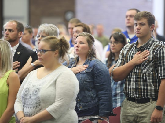 Family members of 645th Regional Support Group listen to the anthem during a ceremony held at the Southfield Pavilion Saturday, July 23, 2016 in Southfield.