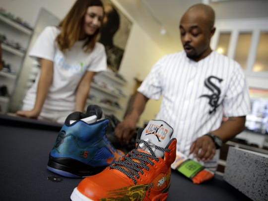 Carl Bradley (right), co-owner of The Luxury Sneaker Exchange on Mass Ave., and Liz Niemiec, founder of Little Wish Foundation, check out a pair of custom shoes to be given to Jaycob Solomon on July 23, 2016.  Pacers point guard Joe Young was on hand to present the shoes.