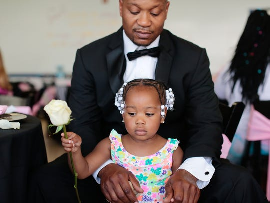 Renay Canty, of Detroit, holds a rose her father James
