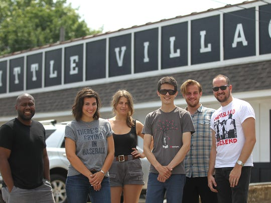 Members of Little Village's staff pose for a photo outside their newsroom on South Dubuque Street on Wednesday, July 27, 2016.