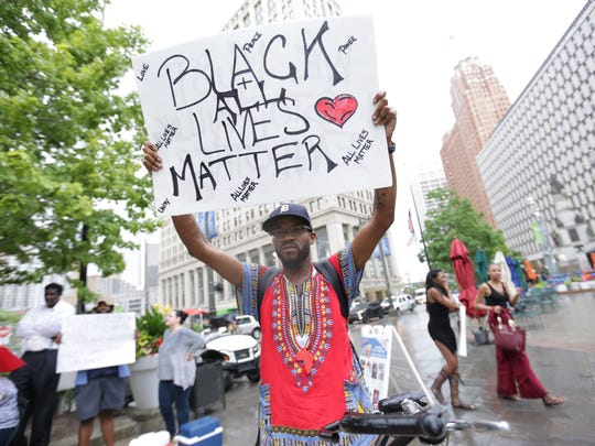 Gerald Thomas, of Detroit, holds a sign in the rain while protesting at Campus Martius in downtown Detroit on Friday July 8, 2016 during a protest of recent shootings involving police officers that led to the deaths of Alton Sterling, 37, in Baton Rouge and Philando Castile, 32, in Falcon Heights, Minn.