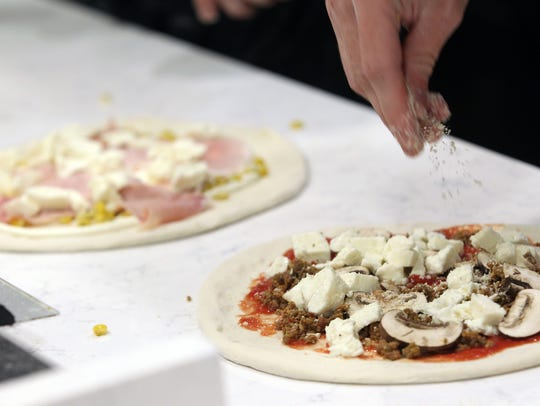 Pizzas are prepared at Red Vespa in Solon on Friday,
