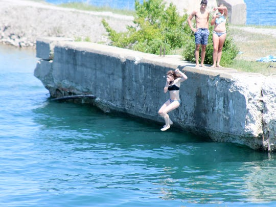 As generations have done before them, Teens jump off an unused pier into the deepwater port on Lake Huron at Rockport State Recreation Area in Alpena, Michigan.