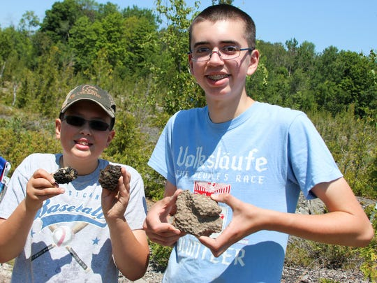 Zachary and Logan Pickelmann, ages 11 and 14, of Frankenmuth, show off their fossil hunting finds at Rockport State Recreation Area in Alpena, Michigan.