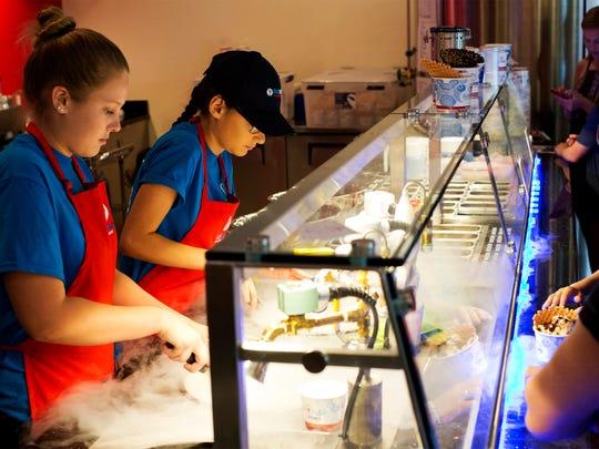 Zainn Eid, left, and Kristin Healey, use liquid nitrogen vapor to freeze ice cream for customers at Sub Zero Ice Cream at the Shoppes at Vanderbilt on July 19, 2015. (Carolina Hidalgo/Staff)