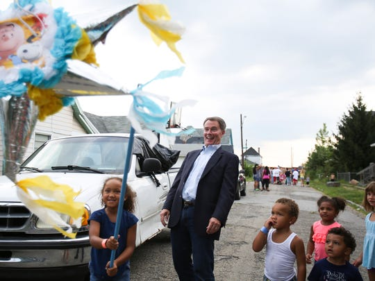 Cerinity Johnson, 5, swings a stick at the pinata as Mayor Joe Hogsett leans back during a block party on E. Regent Street to celebrate National Night Out.