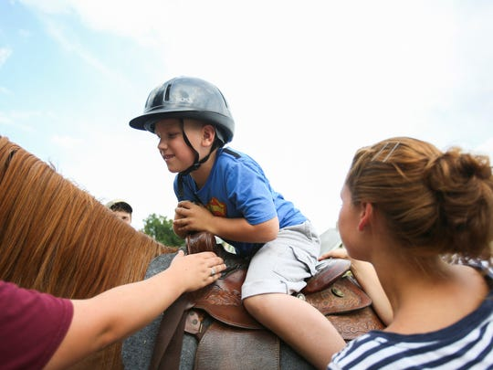 Xavier Sinclair 7, gets on a horse during a block party on E. Regent Street to celebrate National Night Out on Aug. 2, 2016. Police officers and Mayor Hogsett joined the community members for the celebration.