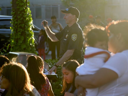 Salem Police Chief Jerry Moore takes a picture of children dancing  during a National Night Out party on Donald St. NE in Salem on Tuesday, Aug. 2, 2016.