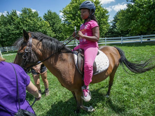 Lea Jones, 11, of Detroit is a student at Burns Elementary and learns to ride a horse for the first time, during the Detroit Horse Power day camp at Ringside Equestrian center in New Hudson, Mich. on Tuesday, July 26, 2016.