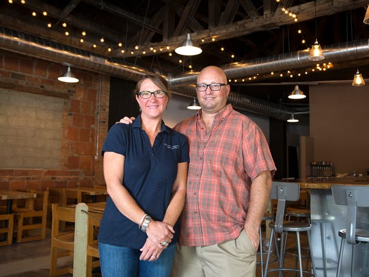 """From left, Angie and husband Chris Weeks pose for a portrait at Wasser Brewing Company in Greencastle, Ind., Wednesday, August 3, 2016. Chris and Angie both have experience as teachers, so when Chris left teaching to pursue opening a brewery, they developed the """"2% for Teachers"""" program which donates two percent of the company's profits to educational programs."""