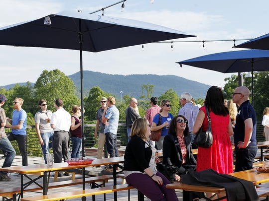 Guests enjoy the open air and views from Highland Brewing's rooftop bar.