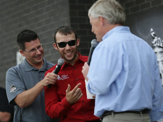 (From left) Kevin Lee holds the microphone for IndyCar driver Bryan Clauson while he is interviewed by Curt Cavin at his annual Carb Day Burger Bash at 96th Street Steakburgers, May 22, 2015.