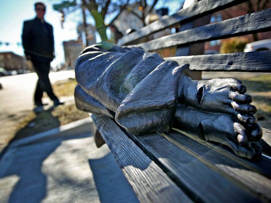 """A blanketed figure on a park bench, with bare and pierced feet, is """"Homeless Jesus,"""" a sculpture at Roberts Park United Methodist Church. The statue, which is a permanent reminder of homelessness in Indianapolis, was created by Canadian artist Timothy P. Schmalz."""