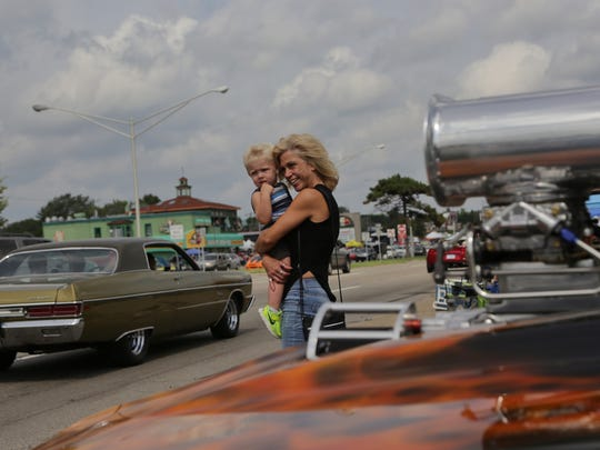 "Annette Felk of Troy holds her grandson Vinny Hughes of Clawson while watching cruisers near her 1967 Chevrolet Camaro SS with a 671 blower she has had 10 years on Saturday, Aug. 20, 2016, during the 2016 Woodward Dream Cruise. ""I love the Dream Cruise. This is our vacation for the whole year. It's five days of nothing but fun,"" Felk said."