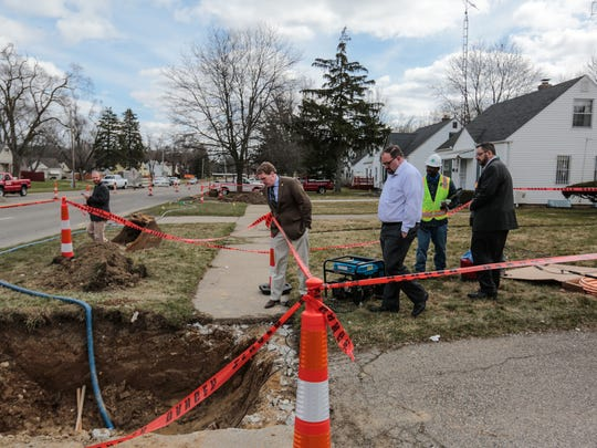 (left to right) Michigan's108th district state representative Ed McBroom, 27th district State Senator Jim Ananich and 36th district state senator Jim Stamas look over the scene where crew members are working on replacing the lead service line from the main to the valve box with a copper line for two houses on Welch Blvd. in Flint on Monday March 21, 2016 as part of Flint Mayor Karen Weaver's Fast Start program to remove Flint's lead-contaminated lines from 30 Flint homes. The representatives that are part of the Joint Select Committee on the Flint Water Public Health Emergency were in town talking to with local residents, pastors and others to work on legislative solutions to the Flint water crisis.
