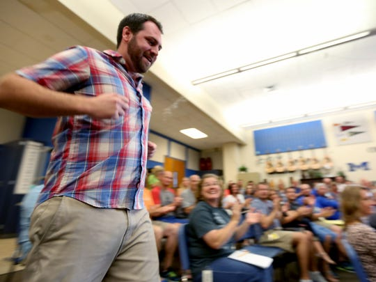 Ben Busch, a new Physical Education teacher, runs through the crowd during a parody new staff draft at McNary High School in Keizer on Tuesday, Aug. 30, 2016.