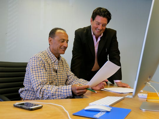 Aaron Levine (right), owner of LG Insurance Agency, works with Ron Tomasian (left), professional insurance agent, at Levine's office in Long Branch.