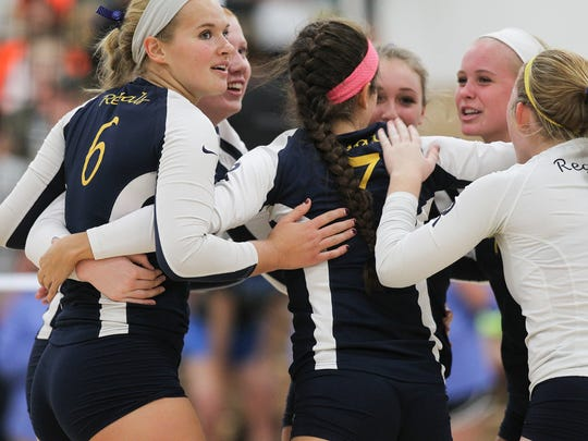 Regina teammates celebrate a point during the Regals' game against Mid-Prairie in Wellman on Tuesday, Sept. 13, 2016.