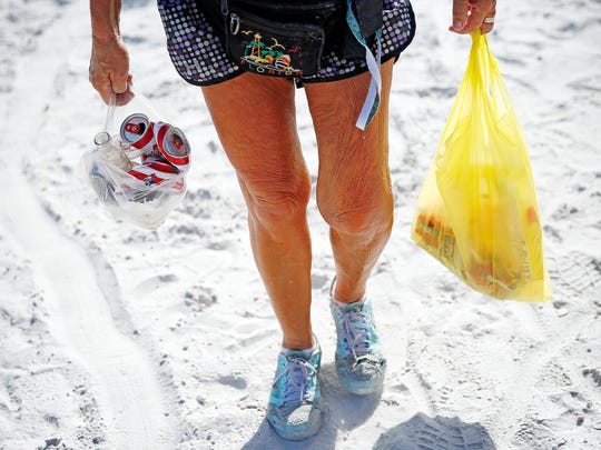 Mary Rose Spalletta of Fort Myers Beach carries cans from her morning walk near Pinchers Crab Shack Sunday, July 5, 2015 at Fort Myers Beach, Fla. Dozens of volunteers came out to the seashore picking up litter from Independence Day festivities, an annual event. The group of volunteers was organized by the Fort Myers Beach Community Foundation. Spalletta was not part of the group, just a conscious citizen. (Corey Perrine/Staff)