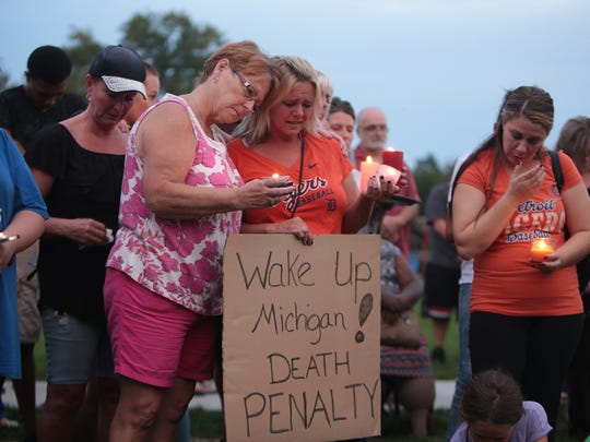 Jill Myslinski (left), of Dearborn Heights, comforts Mary Heady (center), of Dearborn, during a vigil held at Polk Elementary School in Dearborn Heights on Thursday September 22, 2016 near the home where a Dearborn Heights man has been charged with killing four children and torturing his wife.