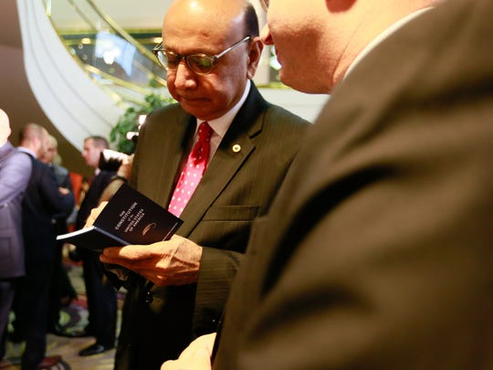 Khizr Khan, father of a Muslim-American Army captain killed in Iraq who offered a challenge to GOP Presidential candidate Donald Trump, signs Dearborn Judge Mark Somers' copy of the Constitution of the United States, during the Arab American Civil Rights League's fifth annual Fight for Justice Gala at the Ford Community and Performing Arts Center in Dearborn on Thursday, Sept. 29, 2016.