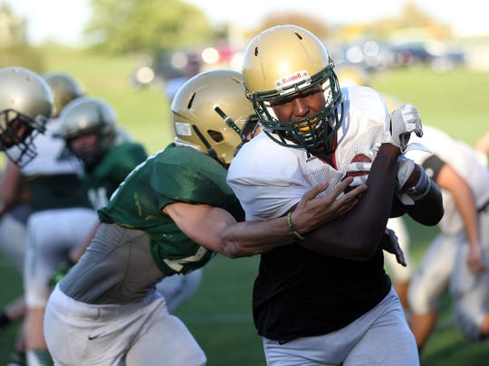 West High's Devontae Lane runs plays with teammates during practice on Tuesday, Oct. 11, 2016.