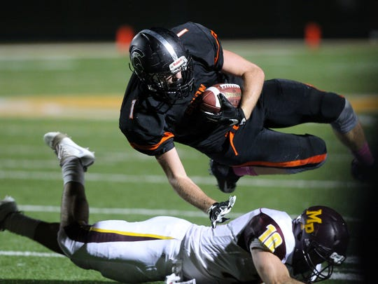 Solon's Jacob Coons gets knocked out of bounds during