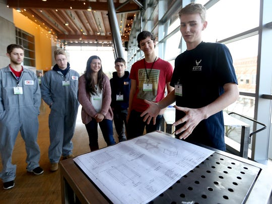 Connor Suderman, far right, a Career and Technical Education Center student from West Salem High School, shows off a weld table he helped to design and build during the Oregon Manufacturers' Summit at the Salem Convention Center on Monday, March 14, 2016. This is the first year for CTEC classes, so students are designing and building many of the items needed to run their workshop.