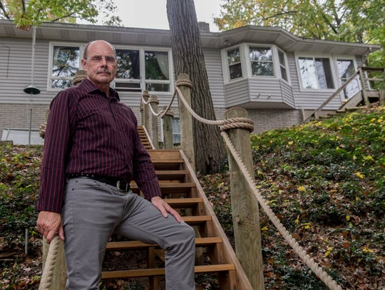 Randy Vallance stands on stairs in his backyard that